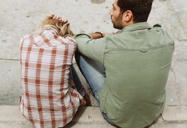 Picture of frustrated couple sitting on sidewalk.jpg