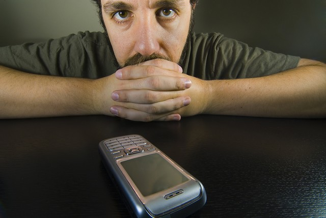 Picture of uncertain man watching phone closely.jpg