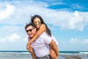 Picture of laughing woman carried piggyback at the shore.jpg