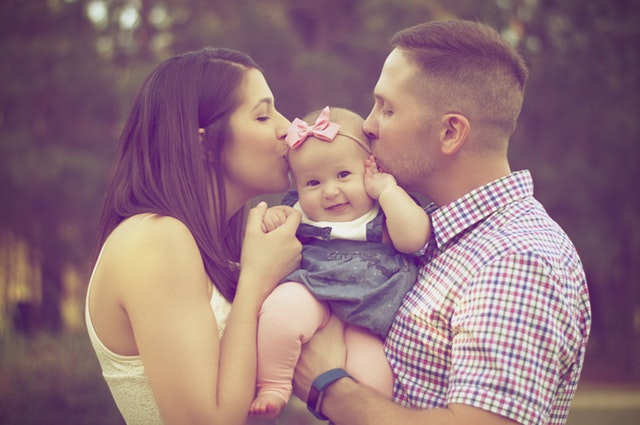 Picture of woman and man kissing their baby.jpg