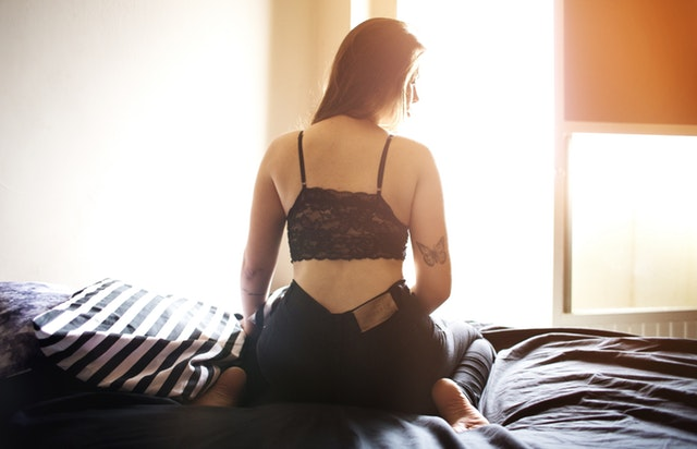 Picture of woman in lace bra and jeans on bed with black sheets.jpg