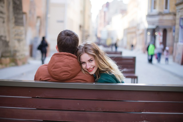 Picture of young woman looking backwards beside man on park bench.jpg
